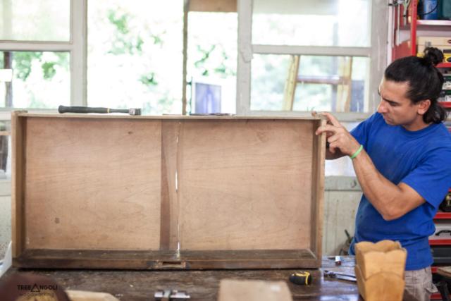 Giacomo al lavoro su un cassetto di un comò da restaurare