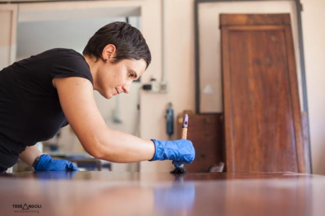 Stefania che applica l'olio paglierino su un tavolo