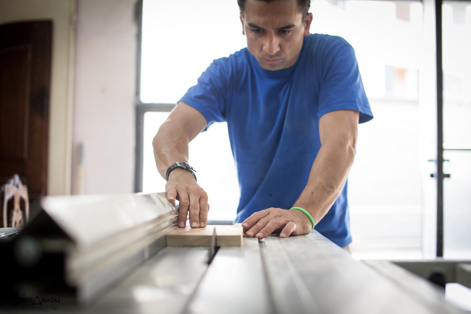 Giacomo concentrato a tagliare un pezzo di legno